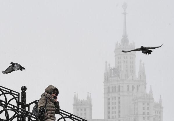 Женщина идет по Таможенному пешеходному мосту через реку Яузу, соединяющему Золоторожскую и Сыромятническую набережные в Москве