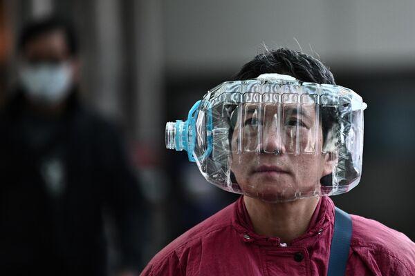 Прохожий с пластиковой бутылкой на лице на улице Гонконга