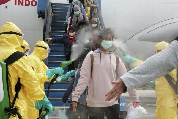 Медицинские работники опрыскивают индонезийских граждан антисептиком после того, как они прибыли из Уханя, в аэропорту Ханг-Надим