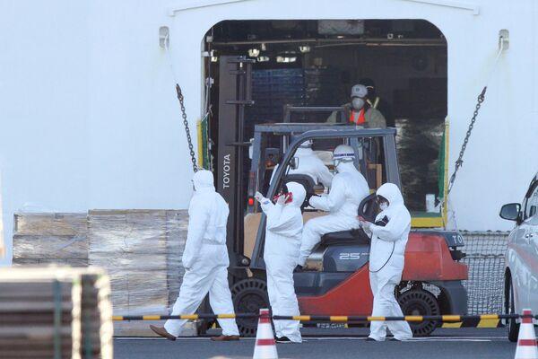 Персонал в защитных костюмах загружает предметы первой необходимости для пассажиров круизного лайнера Diamond Princess в порту Йокогамы