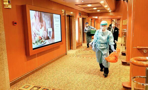 Медицинские работники в защитных костюмах идут на круизном судне Diamond Princess в порту Йокогамы