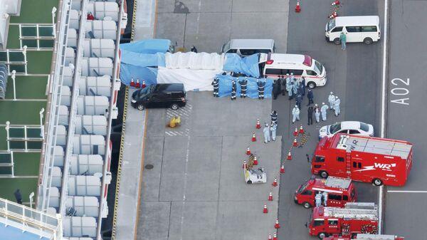 Скорая помощь забирает в больницу людей с круизного лайнера Diamond Princess в порту Йокогамы