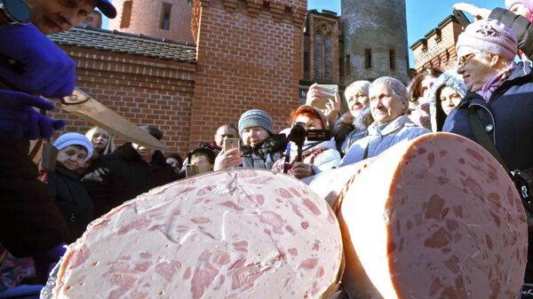 Презентация стокилограммового трехметрового батона колбасы, изготовленного на Гвардейском мясокомбинате  на празднике День длинной колбасы в Калининграде