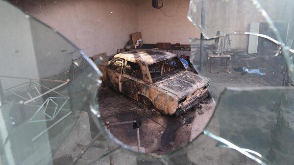 Сгоревшая машина  в селе Блас-Батыр, в 250 км от Алматы, где прошли бесполрядки