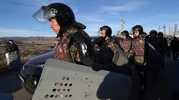 Полицейские идут по дороге возле села Масанчи в 250 км от Алматы 8 февраля 2020