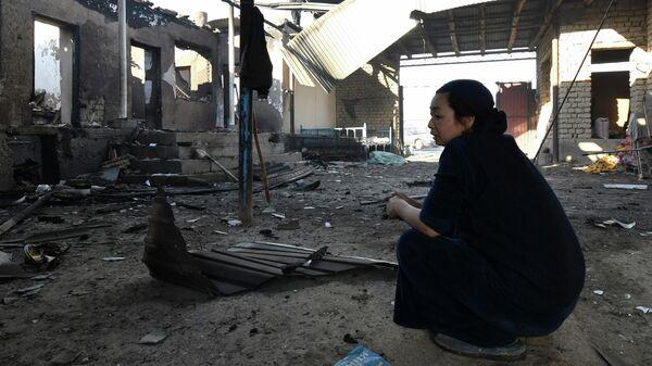 Местная жительница во дворе ее сгоревшего после конфликта дома в Шортубе