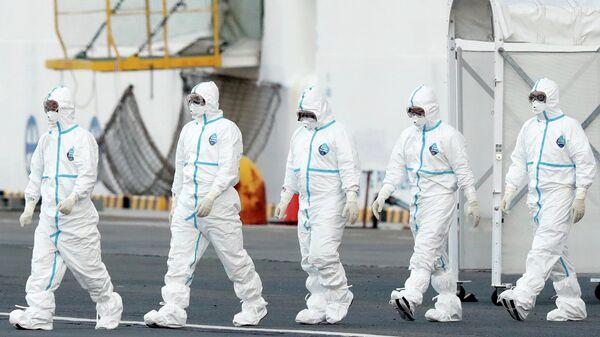 Персонал в защитных костюмах у круизного судна Diamond Princess в порту Йокогамы