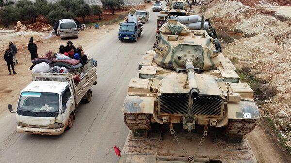 Покинувшие свои дома сирийцы и колонна турецкой военной техники в провинции Идлиб