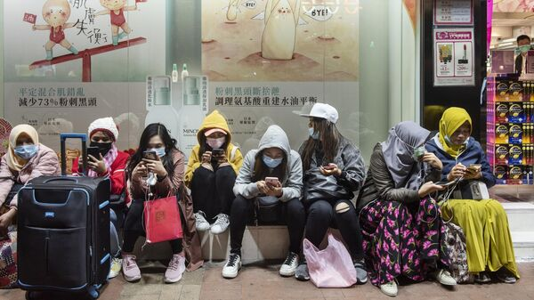 Женщины в защитных масках на одной из улиц в Гонконге