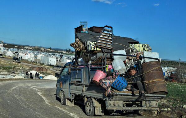 Сирийцы едут в лагерь беженцев, расположенный рядом с границей с Турцией