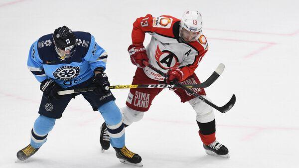 Игрок Сибири Микаэль Руохомаа (слева) и игрок Автомобилиста Павел Дацюк в матче регулярного чемпионата Континентальной хоккейной лиги между ХК Сибирь (Новосибирская область) и ХК Автомобилист (Екатеринбург).