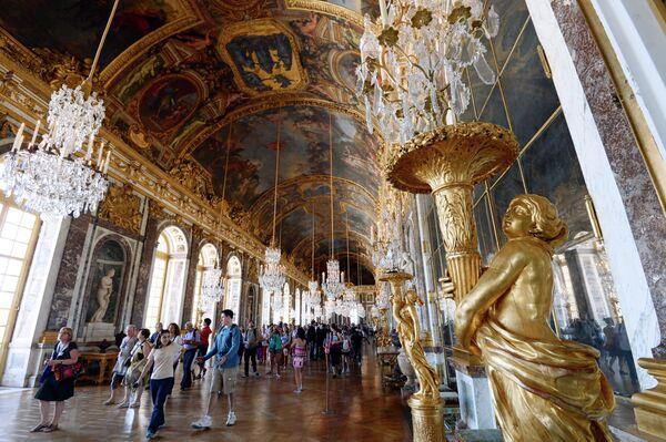 Посетители в Зеркальной галерее Версальского дворца в Париже