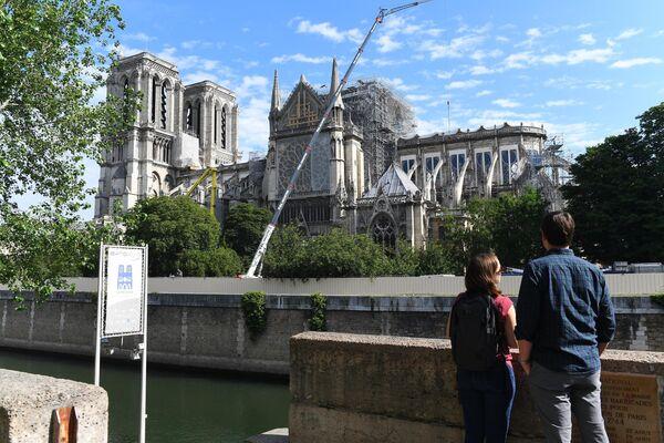 Туристы на набережной Сены у Собора Парижской Богоматери в Париже