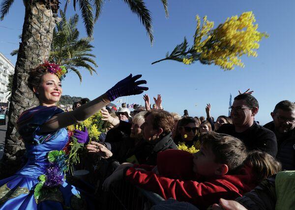 Артистка бросает цветы людям во время парада цветов в рамках 136-го карнавального парада в Ницце, Франция