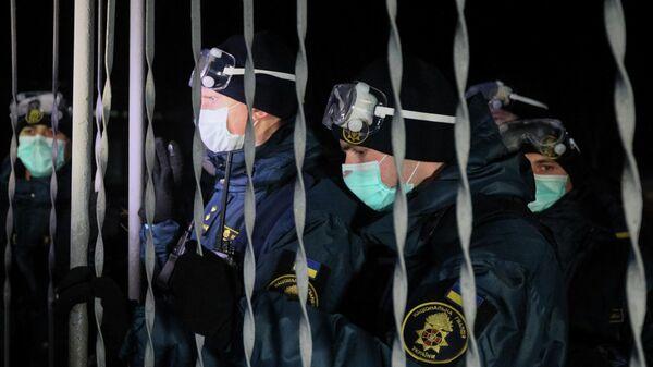 Военнослужащие Национальной гвардии Украины блокируют ворота медицинского учреждения, где планируется держать эвакуированных из Китая
