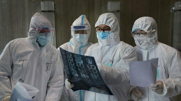 Медицинские работники в защитных костюмах в больнице в округе Юньмэн в провинции Хубэй