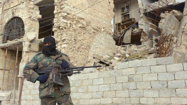 Сирийский военный рядом с разрушенным зданием в Алеппо
