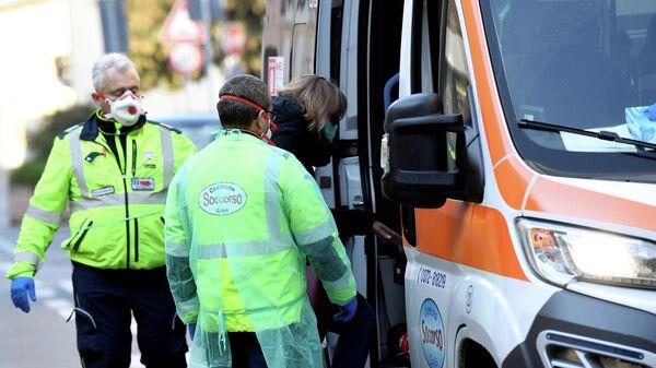 Автомобиль скорой помощи и медицинские работники в итальянском городе Казальпустерленго