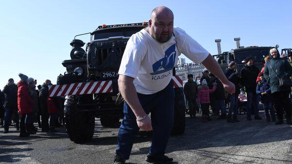 Российский силач Иван Савкин сдвигает с места военную технику во время праздничных мероприятий в честь Дня защитника отечества во Владивостоке