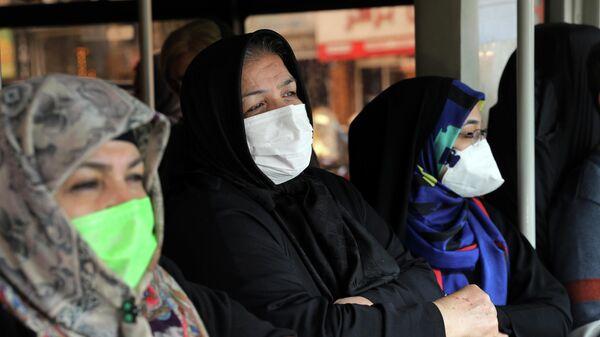 Пассажиры в масках для защиты от коронавируса в общественном автобусе в центре Тегерана, Иран