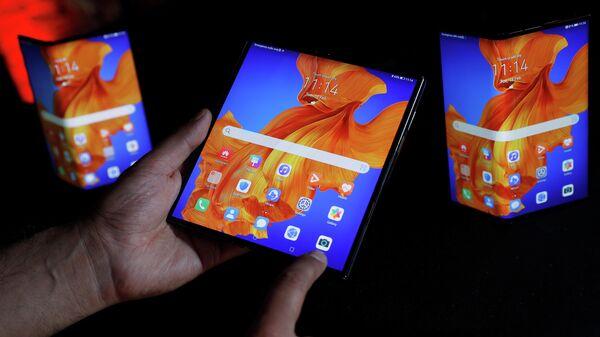 Сотрудник Huawei демонстрирует возможности устройства Huawei Mate XS