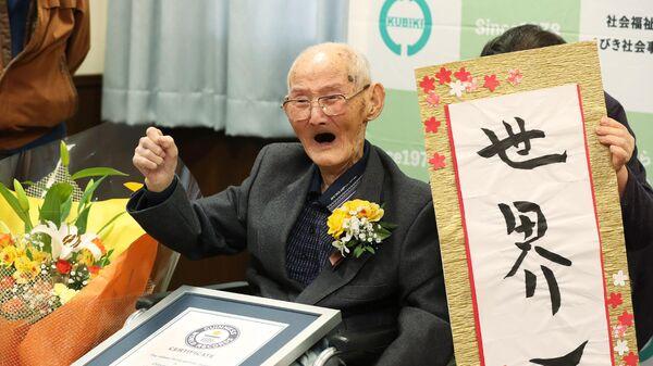 112-летний японец Ватанабэ Титэцу позирует рядом с наградным знаком как самому старому из ныне живущих мужчин