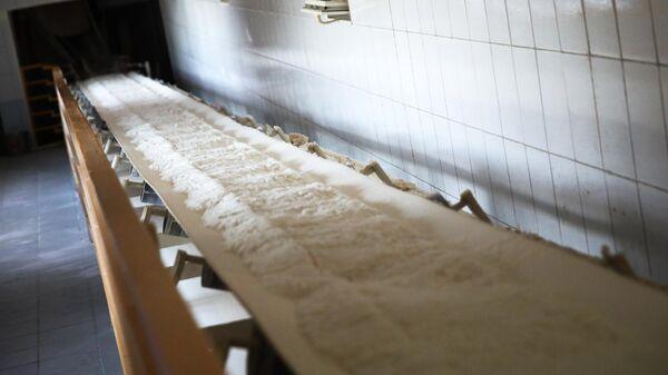 Сахар на конвейерной ленте на сахарном заводе