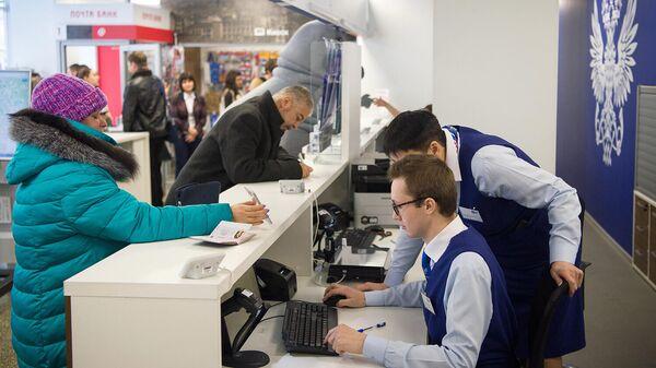 Сотрудники отделения Почты России обслуживают клиентов