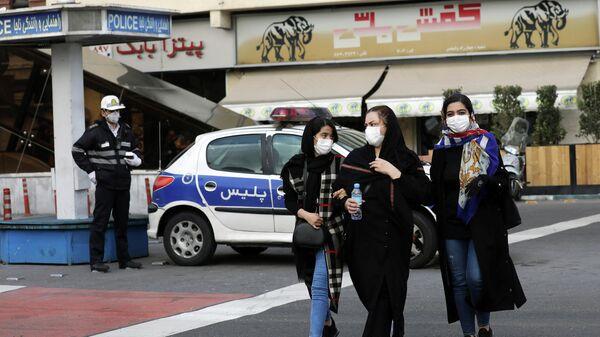 Люди в защитных масках на улице в Тегеране, Иран