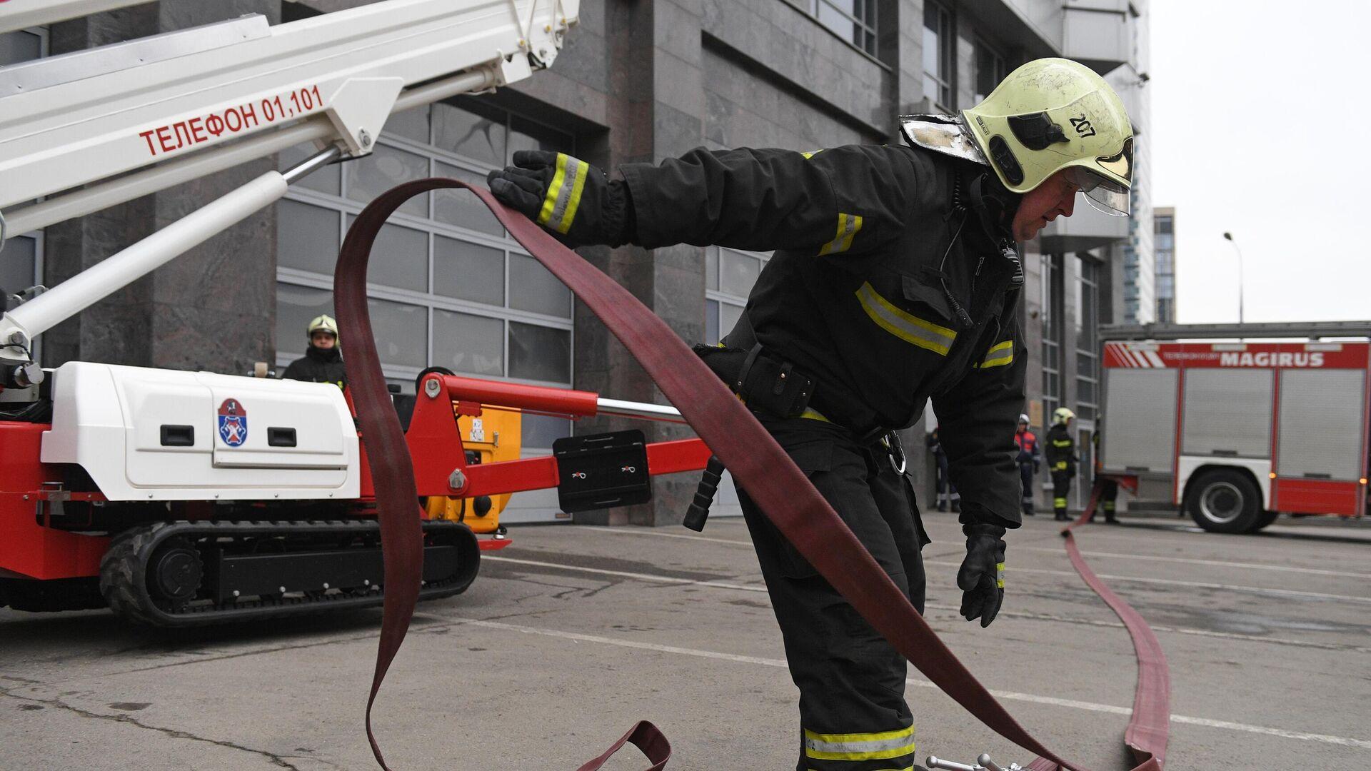 Сотрудник пожарно-спасательного центра Москвы монтирует пожарный рукав - РИА Новости, 1920, 15.11.2020