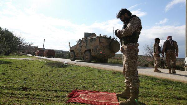 Сирийский боевик во время молитвы у дороги, по которой проезжает турецкий военный конвой в провинции Идлиб