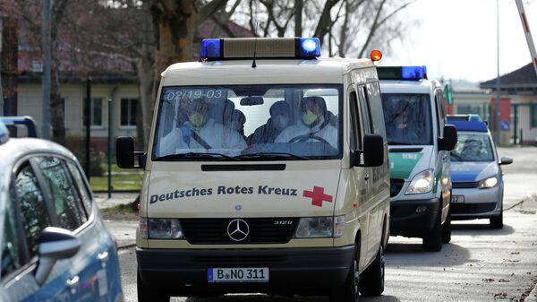 Автомобиль красного креста с эвакуированными из Китая немцами в аэропорту Тегель
