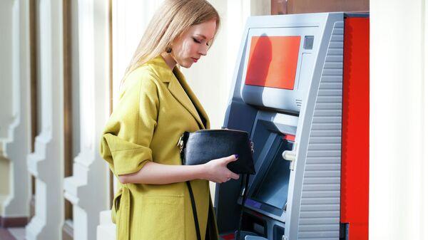 Девушка снимает деньги в банкомате