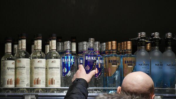 Мужчина выбирает алкогольную продукцию в супермаркете