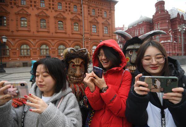Туристы фотографируются с участниками анимационной программы во время открытия фестиваля Московская масленица на Манежной площади