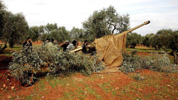 Сирийские боевики заряжают орудие в провинции Идлиб