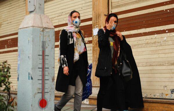 Люди в защитных масках идут по улице в центре Тегерана, Иран