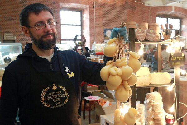 Участник держит в руках сыр на сырном фестивале в Музее Москвы