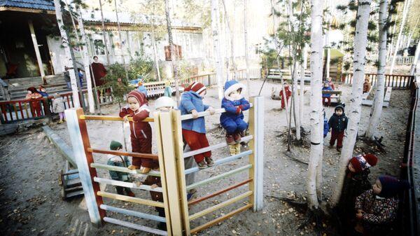 Воспитанники яслей-сада во время прогулки с воспитателем на игровой площадке
