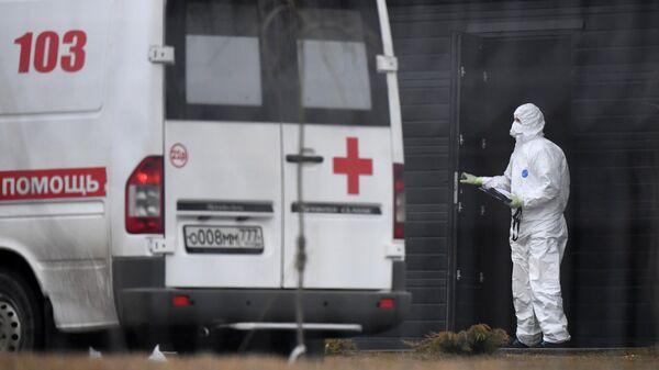 Сотрудник скорой помощи в защитном костюме на территории больничного комплекса в Коммунарке.