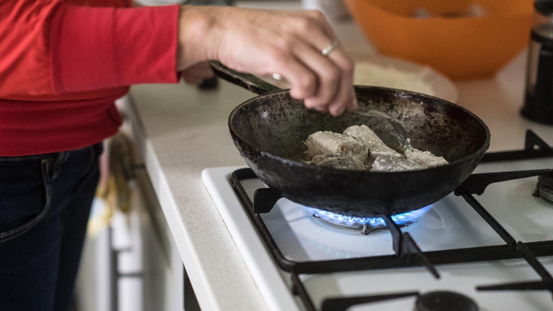 Женщина жарит рыбу на сковородке - РИА Новости, 1920, 05.02.2021