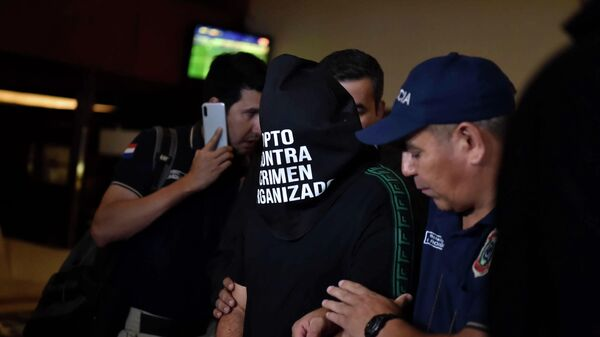 Paraguayan police officers arrest an unidentified man at the Hotel Yacht y Golf Club in Asuncion, Paraguay on March 4, 2020 where two passports with allegedly adulterated contents were seized from the suite where Brazilian footballer Ronaldinho is staying. - Former Brazilian soccer star Ronaldinho and his brother Roberto were wanted by Paraguayan authorities for alleged possession of adulterated passports with which they entered the country, local authorities said Wednesday. (Photo by NORBERTO DUARTE / AFP)