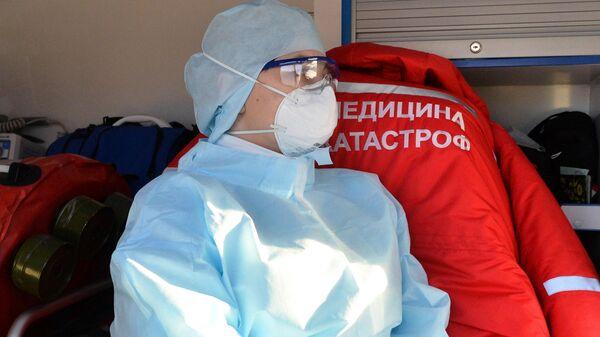Медицинский работник во время учений по проведению медицинской эвакуации пациентов с симптомами коронавируса