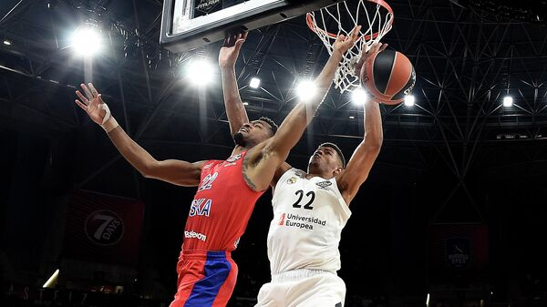 Real Madrid's Cape Verdean centre Walter Tavares (R) challenges CSKA Moscow's US guard Cory Higgins during the EuroLeague semi-final basketball match between CSKA Moscow and Real Madrid at the Fernando Buesa Arena in Vitoria on May 17, 2019. (Photo by LLUIS GENE / AFP)