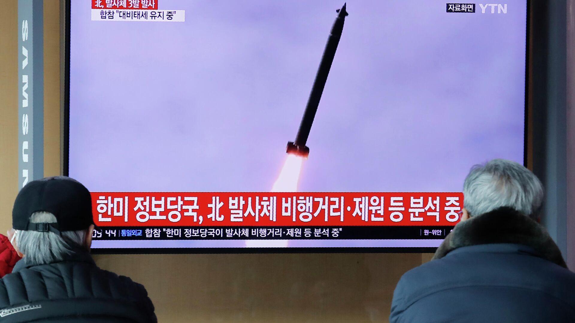 Люди смотрят новости в сеульском метро о запуске ракет в КНДР - РИА Новости, 1920, 25.03.2021