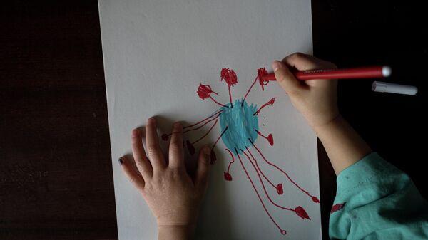 Двухлетний ребенок рисует вид коронавируса под микроскопом