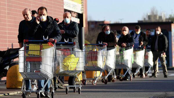 Местные жители возле супермаркета в городе Пьольтелло, Италия