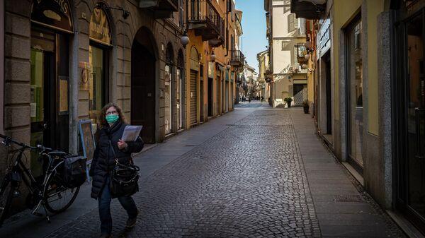 Женщина в маске но одной из улиц Новары