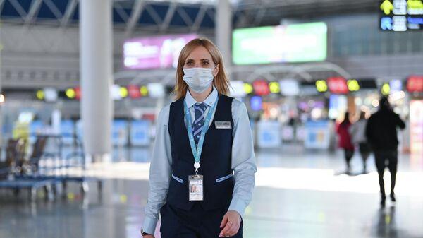 Сотрудница аэропорта в медицинской маске в аэропорту Сочи