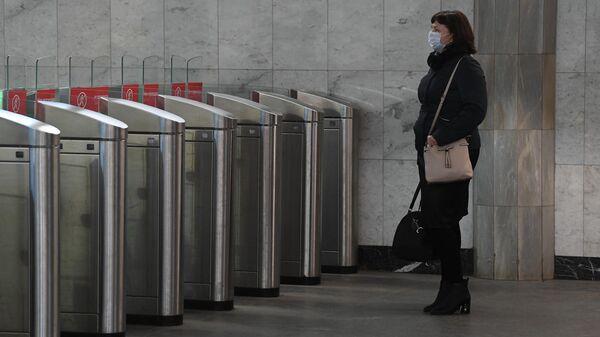 Женщина в медицинской маске на входе в Московский метрополитен